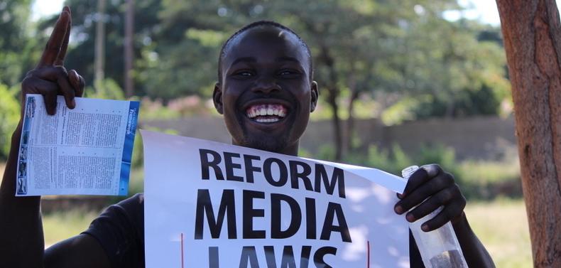 man smiles lifting media freedom poster
