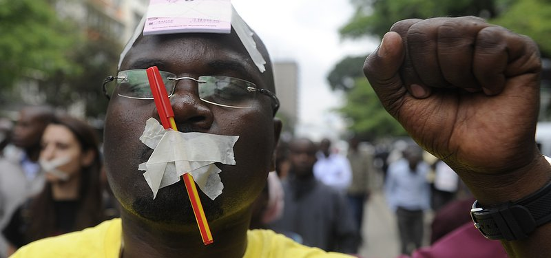A man with his mouth taped closed raises his fist in protest